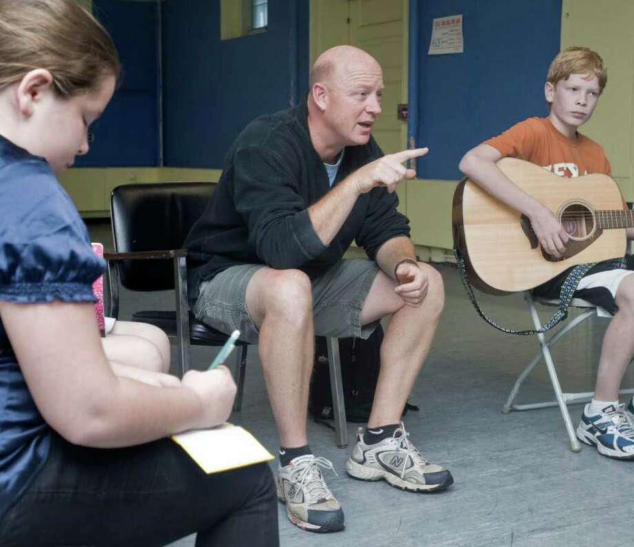 Hunter Julo, 10, of Ridgefield, makes notes as Kevin Briody comments on a song while Sean Honey, 13, of Ridgefield, awaits with his guitar. Emmy-Award winning musician Kevin Briody of Ridgefield is lending his talents to students who yearn to become songwriters. His class includes kids from 10 to 13 years old of Ridgefield, Danbury and North Salem. Thursday, Oct. 28, 2010 Photo: Scott Mullin / The News-Times Freelance