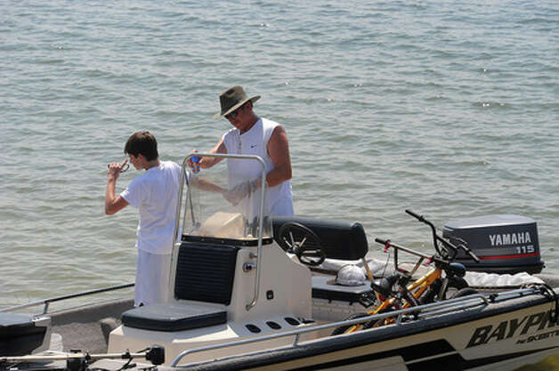 Danny Chambless applies sun screen to Trevor Chambless, 13, before boating on Lake Sam Rayburn on Wednesday. Guiseppe Barranco/The Enterprise