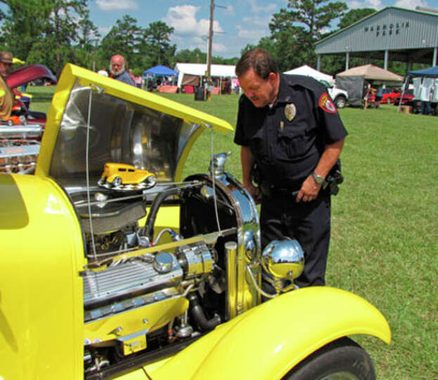 Photo by Charles Kerr  A Kirbyville police officer checks out a vehicle at the Crusin' Kirbyville ev