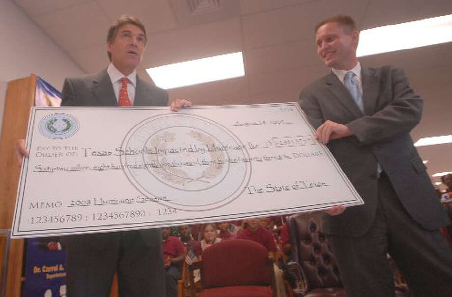 Gov. Rick Perry presents a check for nearly $63 million to Robert Scott, Texas Comissioner of Education, to defray costs from Hurricane Ike and other disasters at Smith Middle School Friday afternoon. Beaumont Independent School District will receive $23 million. Blair Dedrick Ortmann/The Enterprise