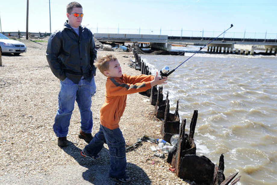 Dustin Perkins, left, and his son Gavin, 7, traveled from Friendswood for a day of fishing at Rollover Pass on Saturday.  Valentino Mauricio/The Enterprise