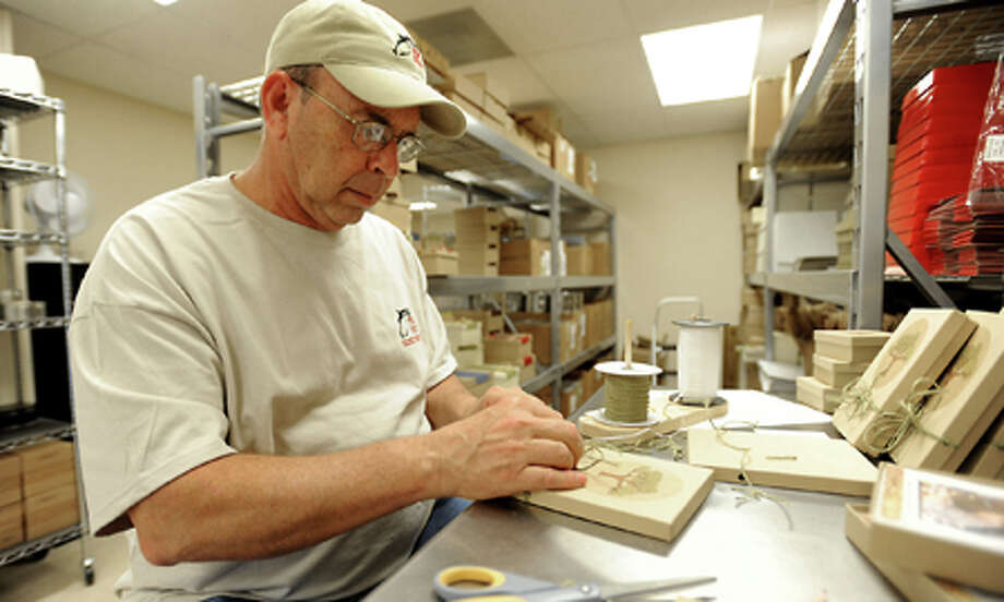 Mike Malone customizes gift boxes for internet order shipments at the Pinto Pony in San Augustine, Tuesday. Tammy McKinley, The Enterprise