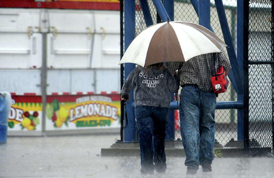 A couple goes to check the opening status of the South Texas State Fair after the opening was postponed due to weather at Ford Park in Beaumont, Wednesday. Tammy McKinley, The Enterprise
