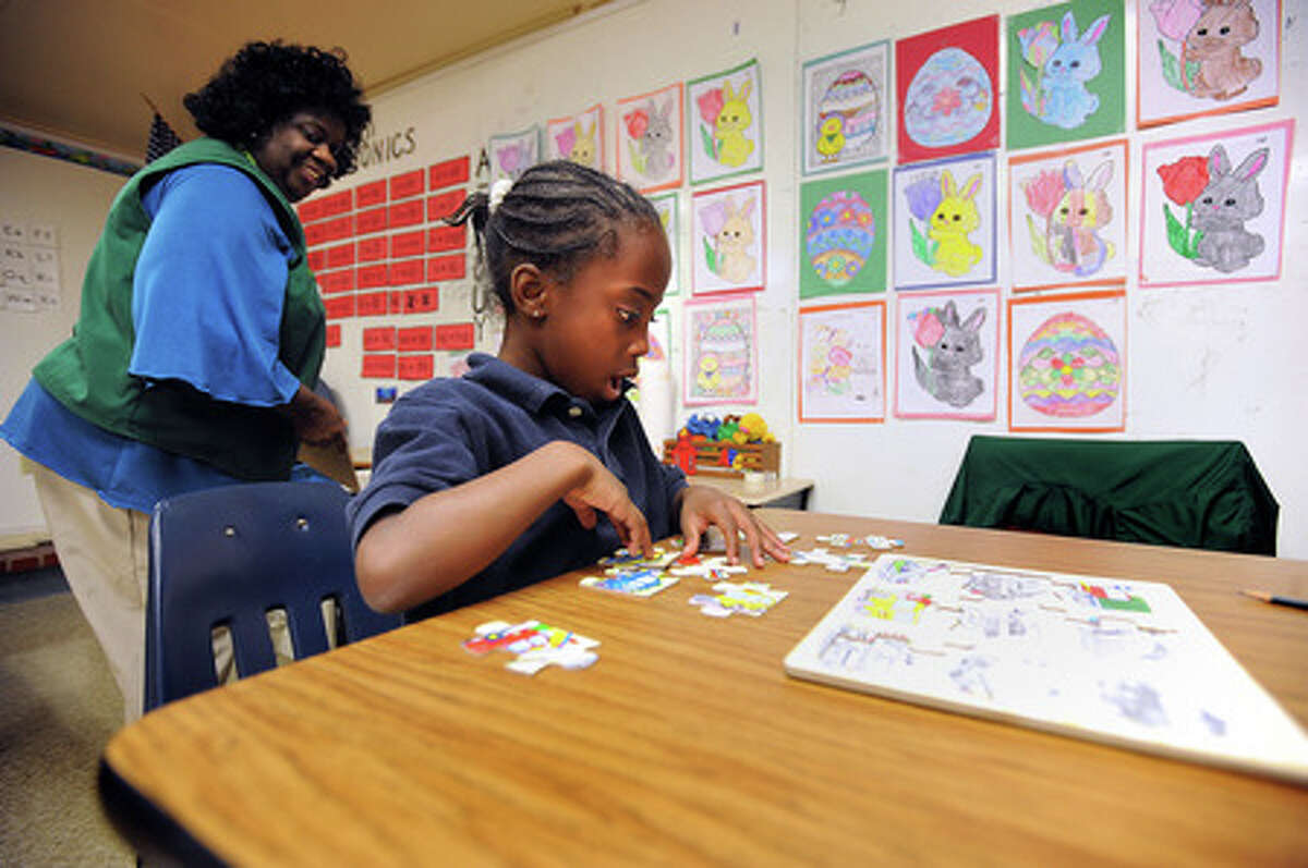 Pearl Ford watches Samyra Porter, 6, finish a puzzle at Travis Elementary on Tuesday. The duo are part of a special program that matches retirees with students in need of tutoring. Guiseppe Barranco/The Enterprise