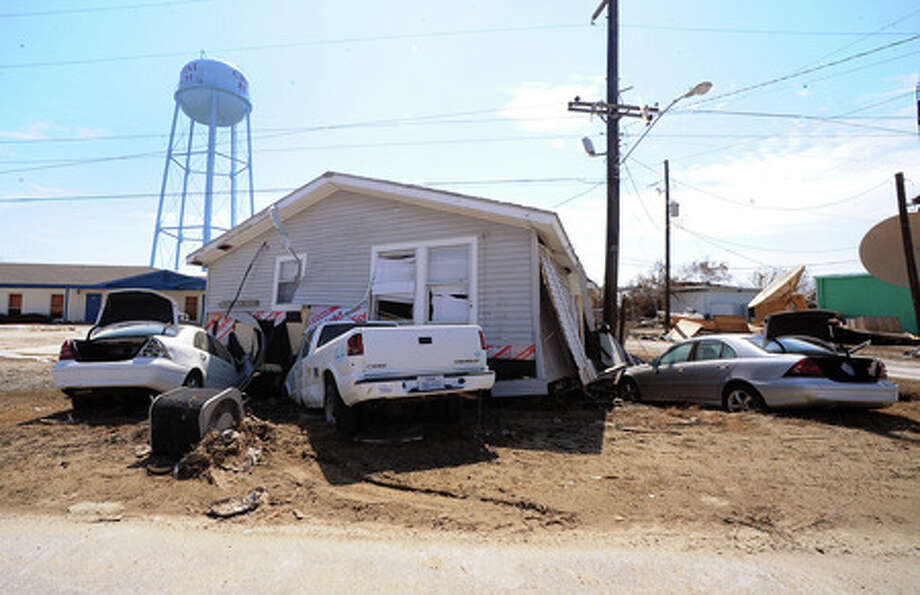 A home rests on cars near the Crystal Beach water tower after Hurricane Ike moved through. Texas coastal residents could pay more for windstorm insurance coverage because of a bill in the state House, but how much more isn?t yet known.  Enterprise file photo