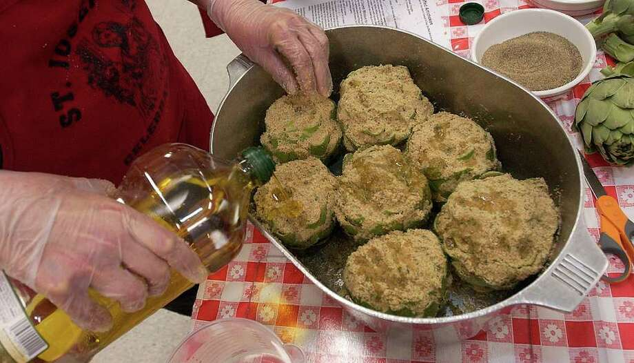 After enough artichokes are stuffed with a breadcrumb mixture, and put into a pan for steaming, Olive Oil and water are poured over them to keep everything moist during the steaming.  St. Anthony Cathedral Basilica is getting ready for their annual St. Joseph Day Alter and Pasta luncheon.   Dave Ryan/The Enterprise