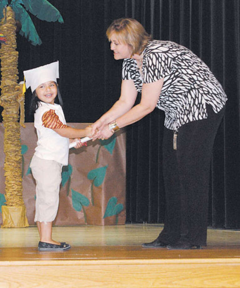 Andrea Gomez accepts her Pre-K graduation certificate from Few Primary Principal Vanessa Phillips during a program Friday, May 22.