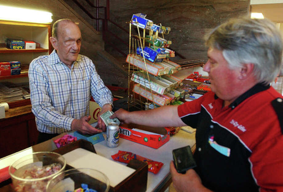Burt Hardwick (left) hands Danny Outler his change from a snacks purchase at Hardwick's concession stand at the Orange County Courthouse on in May 2008. Enterprise file photo