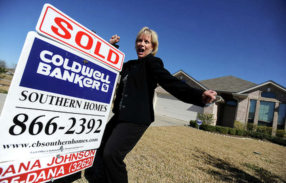 Realtor Dana Johnson poses for a portrait in front of a home she recently sold in Beaumont, Wednesday. The home was on the market for 35 days, bucking the national trend of decreased and delayed home sales. Tammy McKinley, The Enterprise