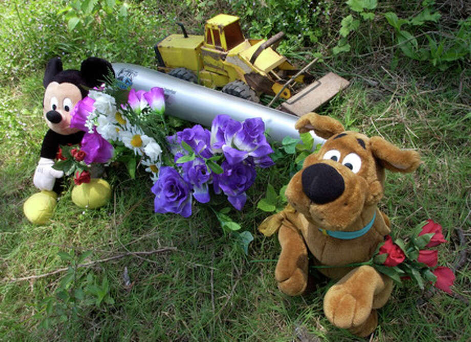 A memorial of flowers, stuffed animals, an inflatable baseball bat and a Tonka tractor sits on the side of the road across from the home of Sheila and Gale Muhs, who are accused in last week's shooting incident in Liberty County.  Dave Ryan/The Enterprise