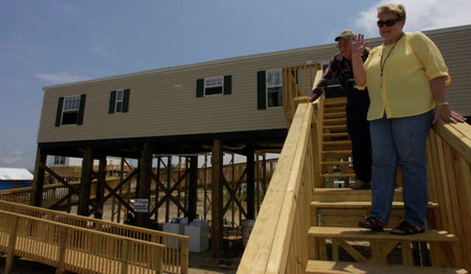 With the long wait over for their newly rebuilt home, which was destroyed by Hurricane Rita in 2005, Dianne Jackson waves goodbye to officials who presented the keys, as husband William Marshall comes down behind her.   Dave Ryan/The Enterprise