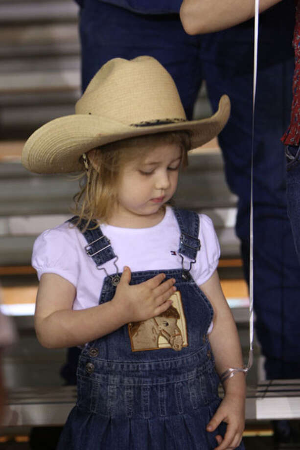 A rodeo cowgirl places her hand over her heart during the national anthem during last week?s Jasper Lions Club Rodeo.