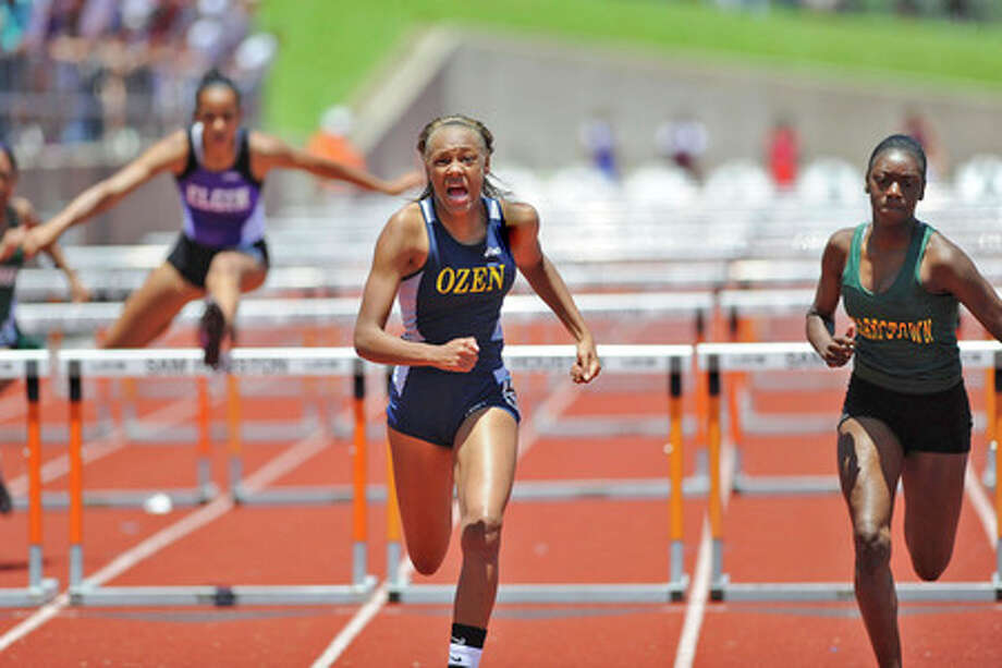 Ozen's A'Lexus Brannon, center,  pushes to the finish line, out running Reysa Whigham of Houston Sharpstown, right, and Desarae Couthren, left,  of Elgin  in the 100 meter hurdles during the Class 4A Region III Track and Field Championships at Sam Houston Universty's Mike Myers complex on Tuesday.  Valentino Mauricio/The Enterprise