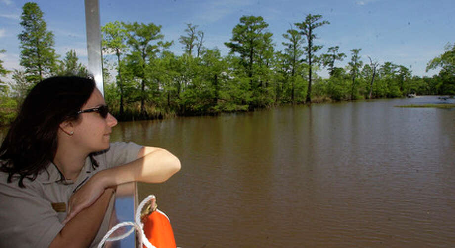 "Deanna Boensch, a National Park Service Ranger, enjoys the view during a boat ride on the ""Cardinal"" as it traveled up Ten Mile Creek off the Neches River.  Dave Ryan/The Enterprise"