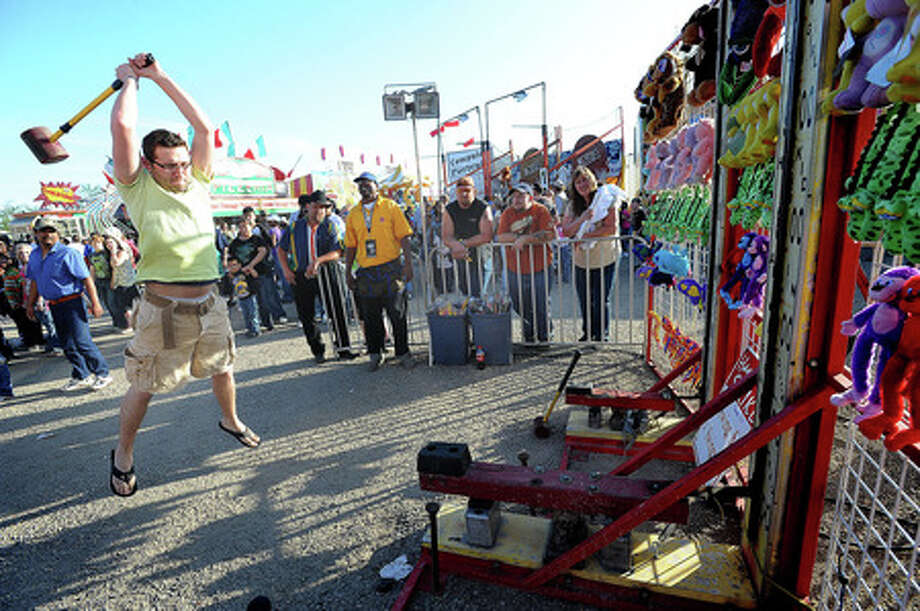 Ryan Smith takes a swing to ring the bell at the South Texas State Fair on closing day. Guiseppe Barranco/The Enterprise