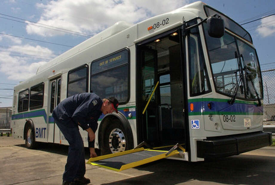 Monty Mills, an A Level Diesel Mechanic at the Beaumont Municipal Transit facility, demonstrates how the new kneeling buses have adjustable wheelchair ramps that will adjust to any curb height.  Dave Ryan/The Enterprise