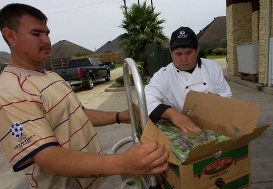 Bistro LeMonde Executive Chef Luis Garcia, right, looks over boxes of fresh vegetables delivered Thursday to the restaurant by Jose Torres, left, of Enrique Montes Distributors.    Dave Ryan/The Enterprise