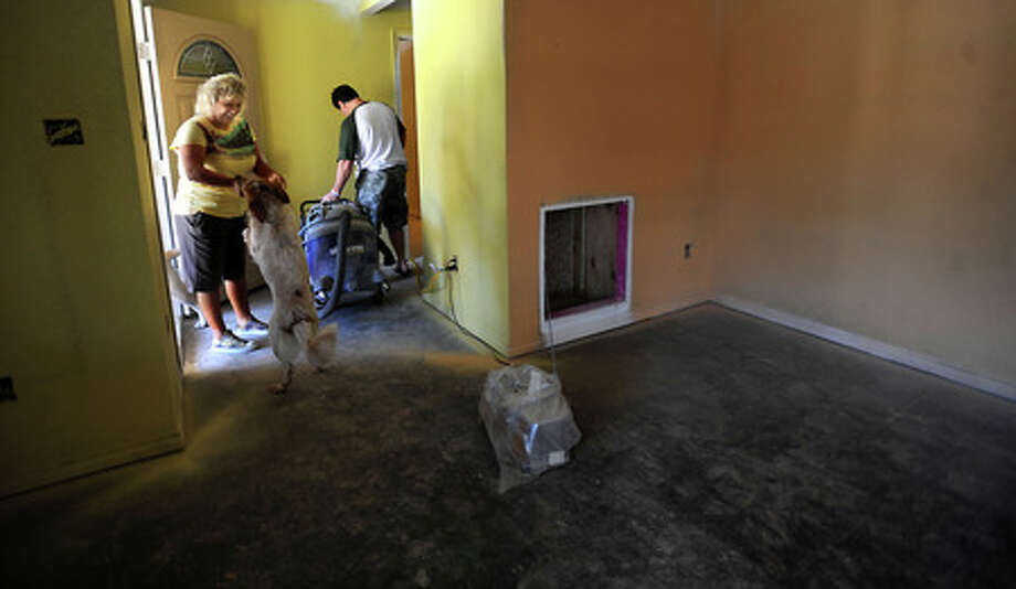 Shawna Gauthier plays with Walley as Michael Gauthier drags the dust vac into another room to continue working on thier home in Bridge City, Orange, Thursday. Tammy McKinley, The Enterprise