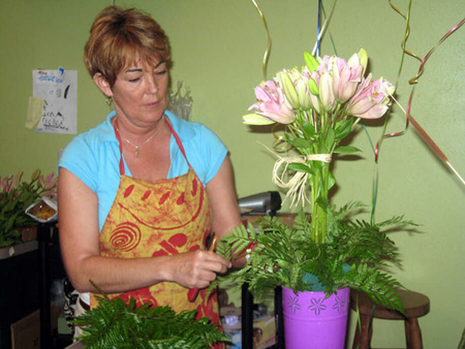 Cambie Jenkins, a designer at Forever Yours Florist, puts together a topiary arrangement for Mothers Day. The arrangement is one of the shop's most popular for the holiday. Heather Nolan/The Enterprise