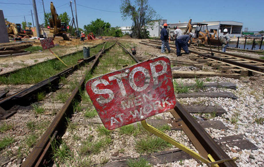 Railroad workers from Econo-Rail Corp, right, work on railroad tracks that were pulled up Monday morning at the intersection of Elizabeth and Cypress street.   In the background, Reytec workers monitor the pumps working to drain off the rainwater inside existing drainage boxes.  Dave Ryan/The Enterprise