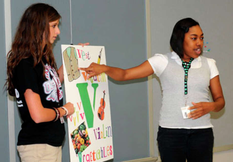 Valerie Dufner and Erica Johnson, above, teach a lesson about the letter V.