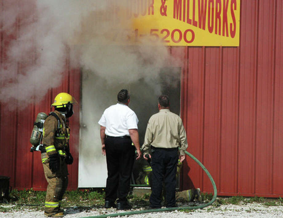Firefighters and personnel from the Lumberton and Beaumont Fire Departments work to contain large structure fire at the Extreme Door and Millworks business located at 4562 U.S. 69 S. in Lumberton Monday morning. Lluvia Rueda/The Enterprise
