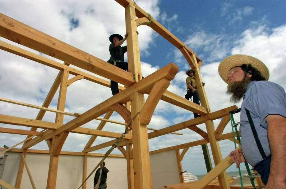Danny Schwartz, right, is an Amish builder from Missouri who is in Crystal Beach rebuilding the two story beach home of Blake Rising using traditional Amish style framing.  His two sons, Pete, left, and Emanel, right, do a lot of the high work as their father directs from the first floor.  Dave Ryan/The Enterprise
