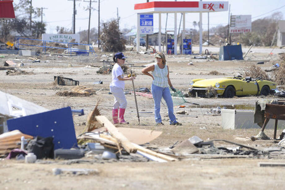 Janet Cox, left, and Kim Barksdale, right, search through surge debris at Crystal Beach for any signs of their possessions after their homes were destroyed by Hurricane Ike.  Sunday, September 28, 2008. Valentino Mauricio/The Enterprise