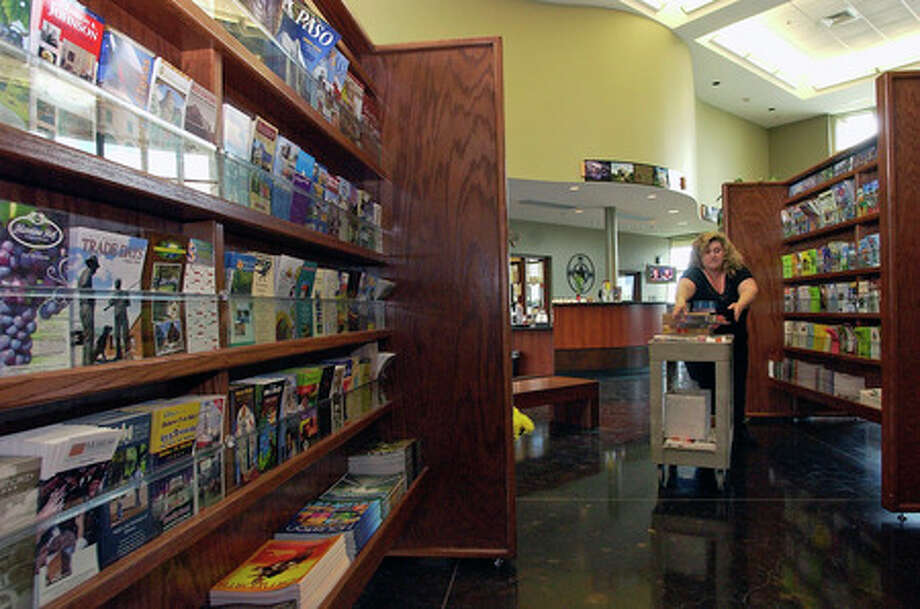 Kathi Hughes, Director of the Ben J. Rogers Regional Visitors Center,  puts out more brochures and pamphlets for the main information rack displays in the lobby.  Dave Ryan/The Enterprise