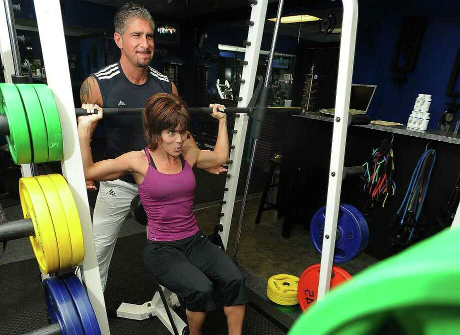 Chad Feldman assists Heather Ross during her workout at Feldman Fitness on Wednesday, April 15, 2009 Guiseppe Barranco/The Enterprise