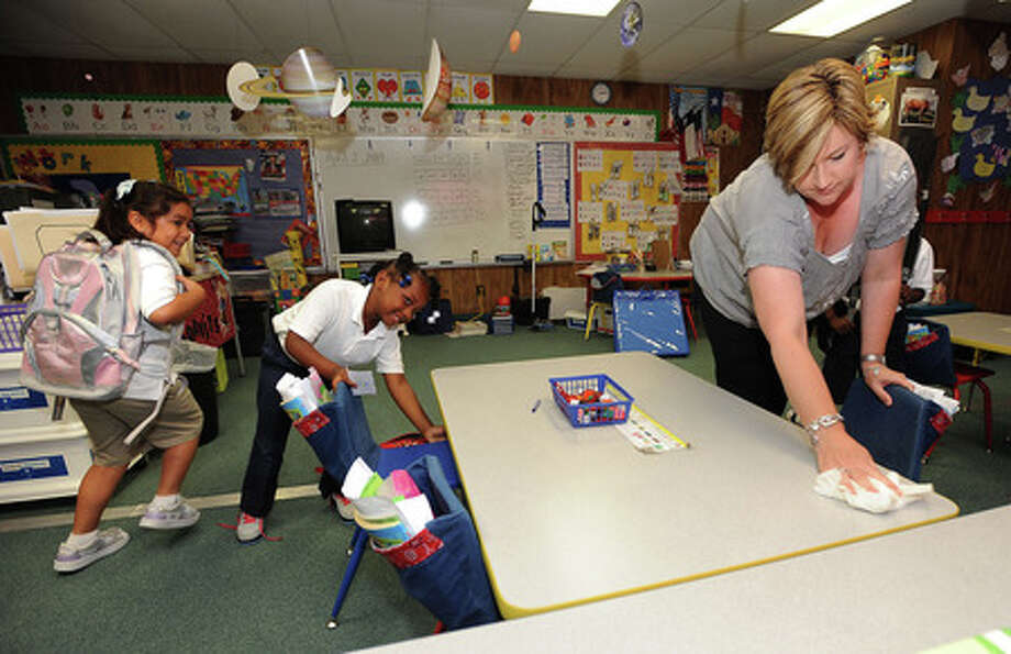 Shane Moravits sanitizes her kindergarden class room as students scamper out at the end of Wednesday's school day at Ehrhart School in Beaumont. For more than two years school policy has kept enrollment up by reducing the number of germs in classrooms. Guiseppe Barranco/The Enterprise