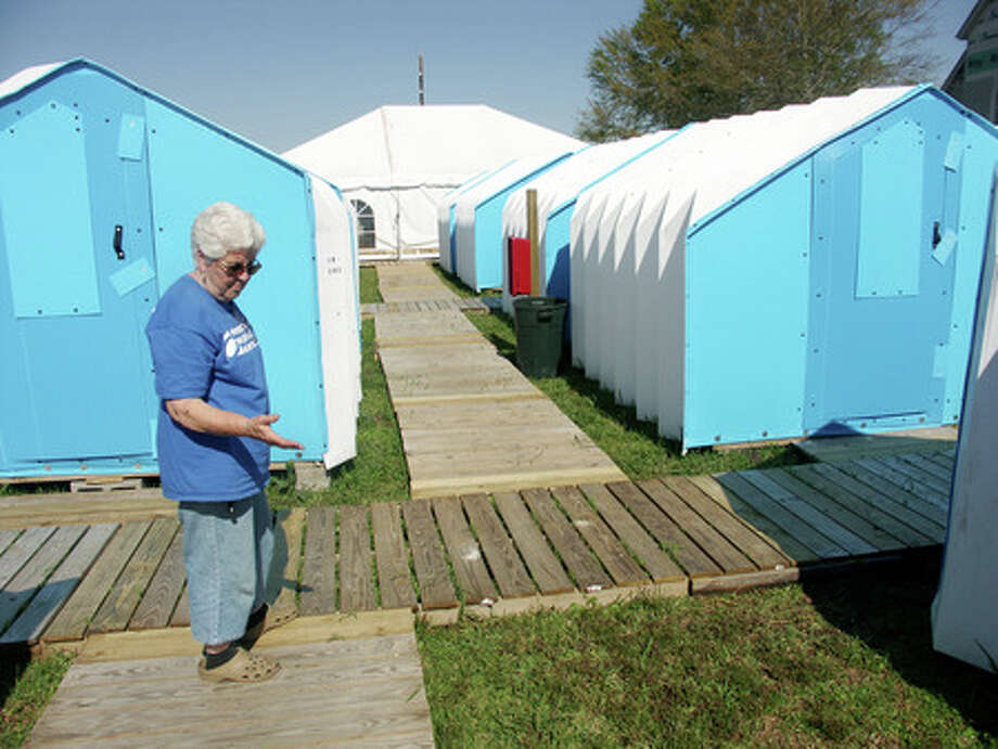 Marilyn Marble, a Presbyterian Disaster Assistance village manager from the Detroit area, stands on the wooden-plank walkway between the temporary village pods behind the Trinity Presbyterian Church in Port Neches. Each pod has both heating and cooling run to it and can house two volunteers. Photo by Greg Hayes/The Enterprise