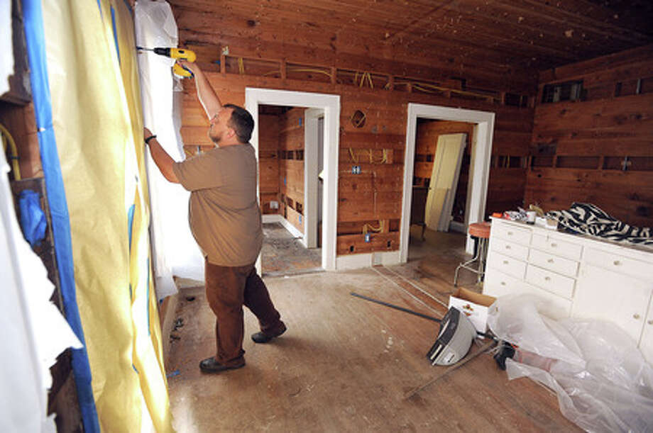 Hunter Bothe drills holes in shiplap walls for inspectors to ensure spray foam fills the entire cavity. The foam will help insulate the home and reduce energy consumption. Guiseppe Barranco/The Enterprise