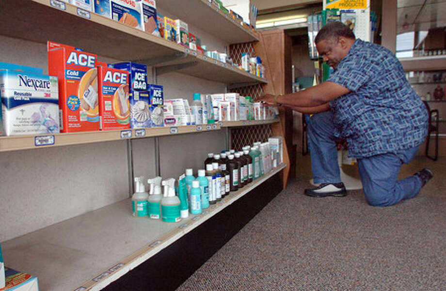 Wesley Young checks out the first aid supsplies near the empty shelf where allergy and dust mask are usually displayed at Lovoi & Sons Pharmacy in Beaumont Thursday. The pharmacy, like many in the area, has sold out of the masks due to the swine flu scare. Pete Churton/The Enterprise