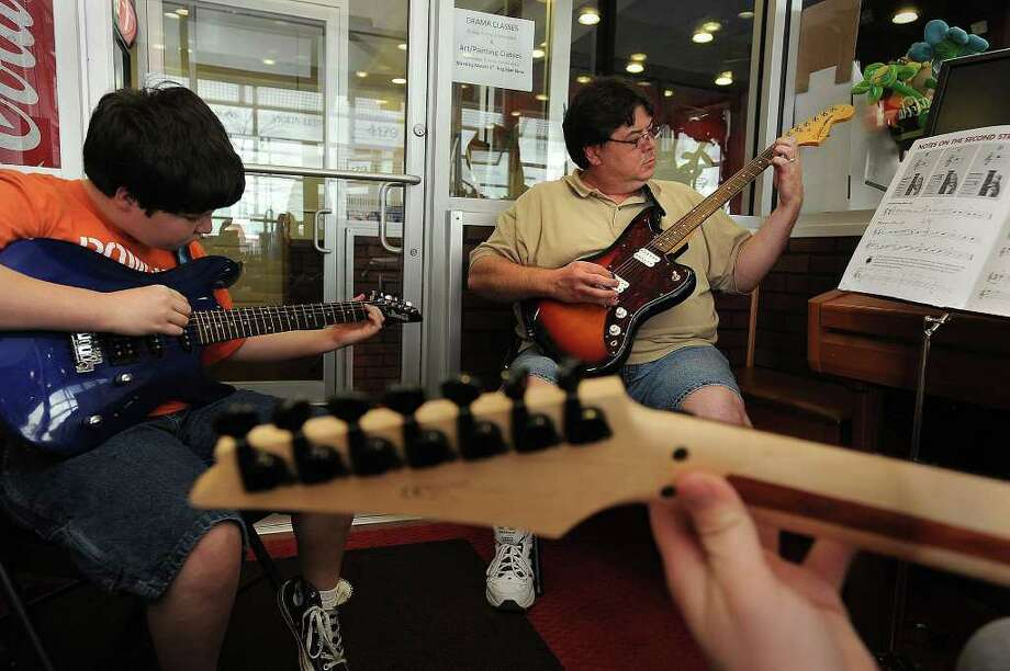 From left, Michael Mouton, 10, and John Mouton learn to pick guitar strings during Michael Moore's class at the Texas Academy of Music, Inc. Guiseppe Barranco/The Enterprise