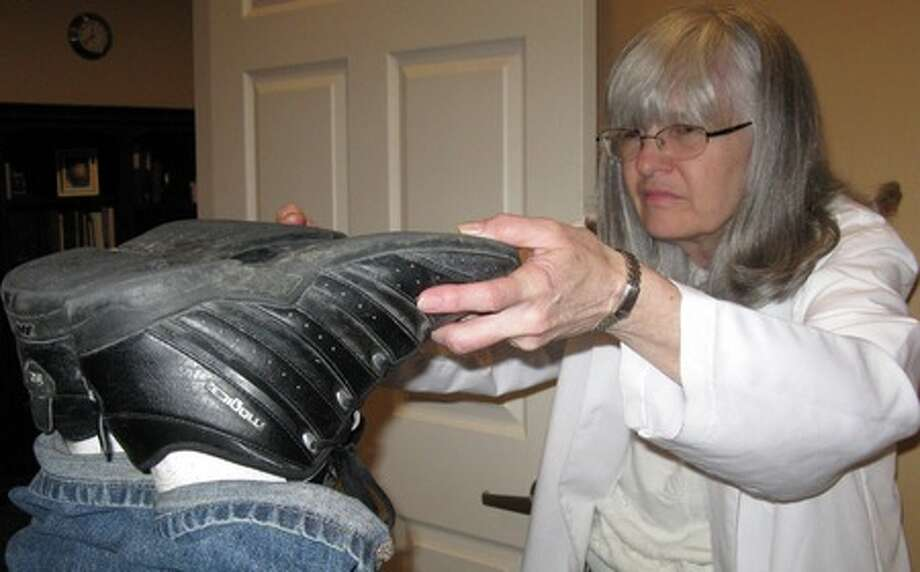 """Dorothy """"Dot"""" Moore, 63, checks to see if Eric Juman's feet are even as part of the activator chiropractic technique, where the bones are properly aligned using a spring-loaded device. Amy A. Collins/ The Enterprise"""