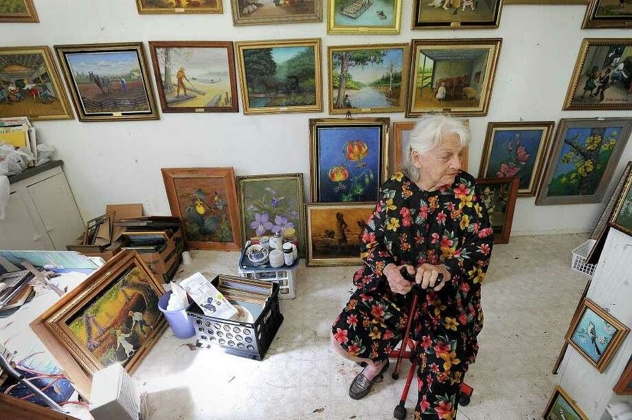 Surrounded by her works of art, Geraldine Watson sits in a gallery near her self built home on Lake Hyatt on Tuesday, April 14, 2009. Guiseppe Barranco/The Enterprise
