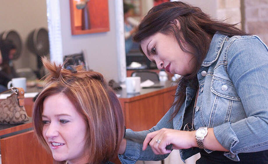 """Jazmin McCurley, right, a Hairstylist at the On Stage Hair Salon, combs some of the hair belonging to Emily Patrizi, who was having it cut into a """"Stacked Bob"""" style for the summer.   Dave Ryan/The Enterprise"""