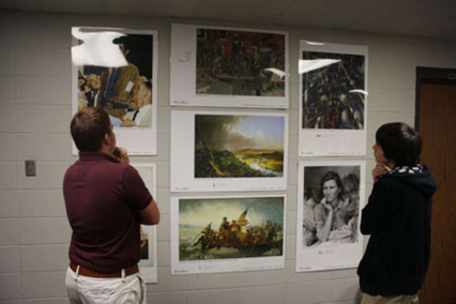 Colby White, left, and Jason Hargrove view some of the Picturing American art reproductions on display at the Jasper High School library