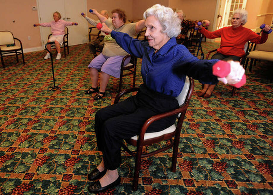 Bettye Tompkins chair exercises at Calder Woods retirement community on Monday. Guiseppe Barranco/The Enterprise