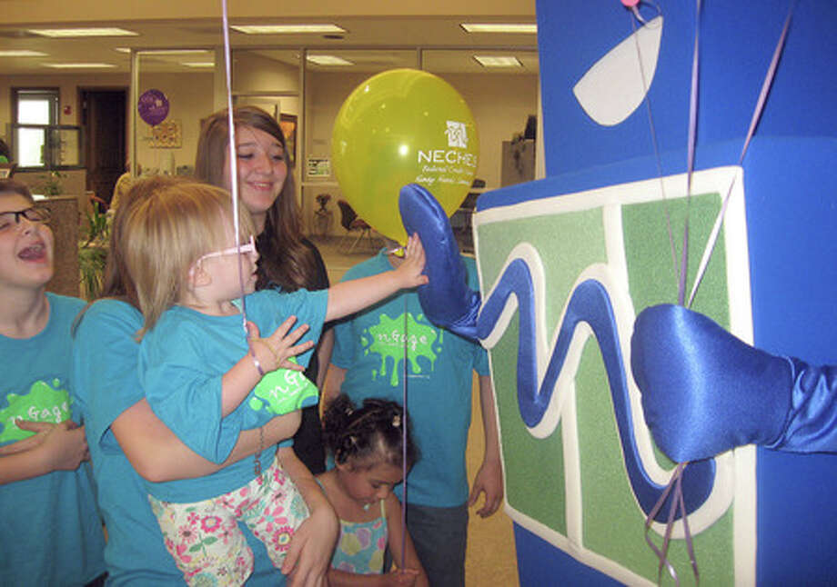 Kailyn Brown, 1, gives the Neches Federal Credit Union mascot, nCredible, a high five at the credit union on Thursday. Neches Federal Credit Union has three youth programs designed to help children and young adults learn about finances. Heather Nolan/The Enterprise