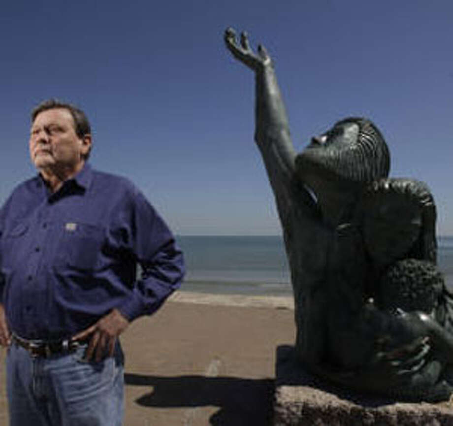 Flanked by the memorial to the Great Storm of 1900, oceanographer William Merrell dreams of a protected coast.   Melissa Phillip/Chronicle