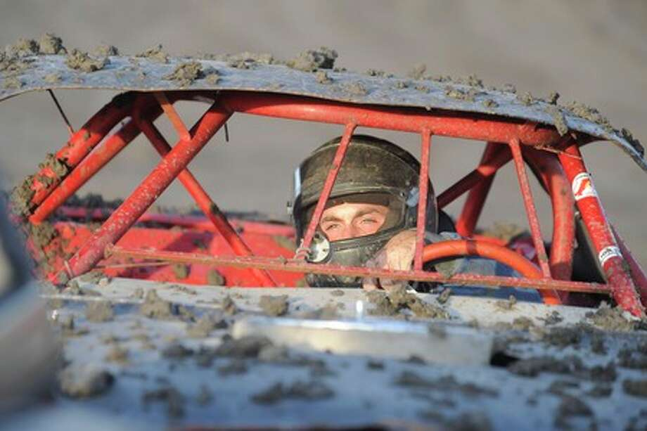 A stock driver covered in mud leaves the track after testing the tacky dirt track during hot lap runs  at Golden Triangle Raceway Park.  Valentino Mauricio/The Enterprise