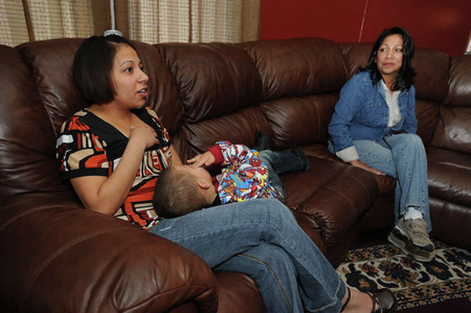 Lenore Coleman holds Joshua Coleman, 3, while talking about her time in the military. Coleman's mother Rose Gray listens. Coleman is one of four sisters who served in the military. Guiseppe Barranco/The Enterprise