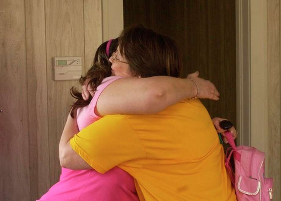 Laura Havard, right, receives a congratulatory hug from Beth Bakker, a local pastor who knew her in prison and had come to see her at the Just Out Fresh Start Shelter.     Dave Ryan/The Enterprise