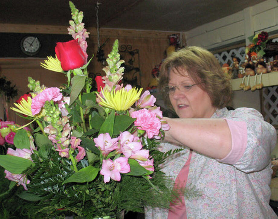 Kay Castilaw arranges a bouquet of flowers at Grapevine Florist and Gift Emporium in Kountze. Castilaw started her career at a florist in Beaumont about 25 years ago and has worked at Grapevine for the past year. Amy Collins/The Enterprise