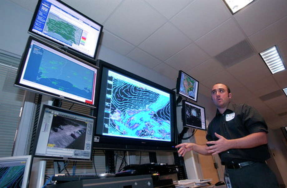 Meteorologist Mike Griffin, with the National Weather Service in Lake Charles, explains the information shown on the different monitors in the Operations room during the open house-tour Friday morning.  Dave Ryan/The Enterprise