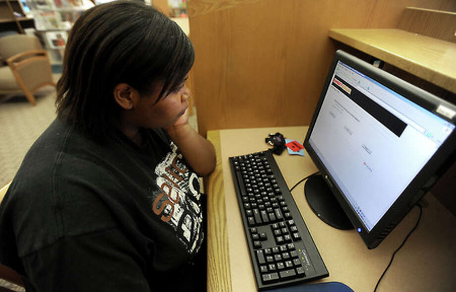 Keosha Sears applies for a job at the Family Dollar from the computer station at the Elmo R. Willard Library in Beaumont, Thursday. Tammy McKinley, The Enterprise