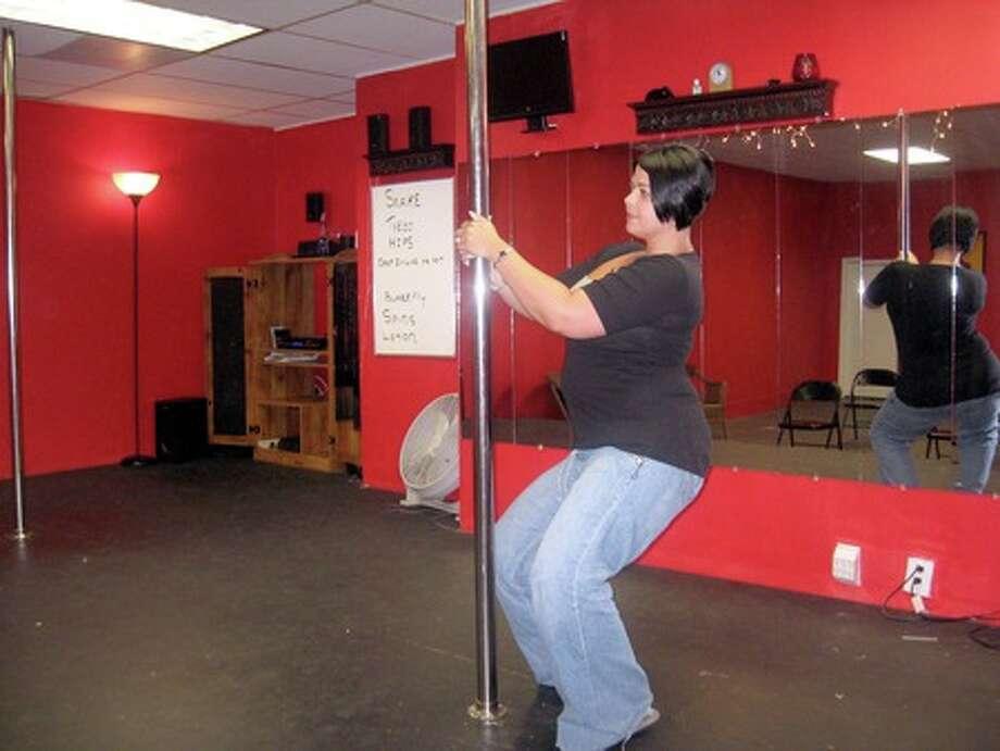 Nicole Moak, owner of Stilettos in Port Neches, shows a beginner?s aerobics move. Moak teaches women pole fitness classes at the aerobics studio. Heather Nolan/The Enterprise