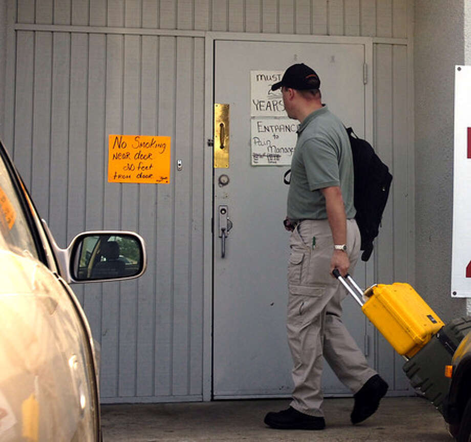 An officer involved in a regionwide raid enters a suspected pill mill in Orange in June, 2007. Enterprise file photo